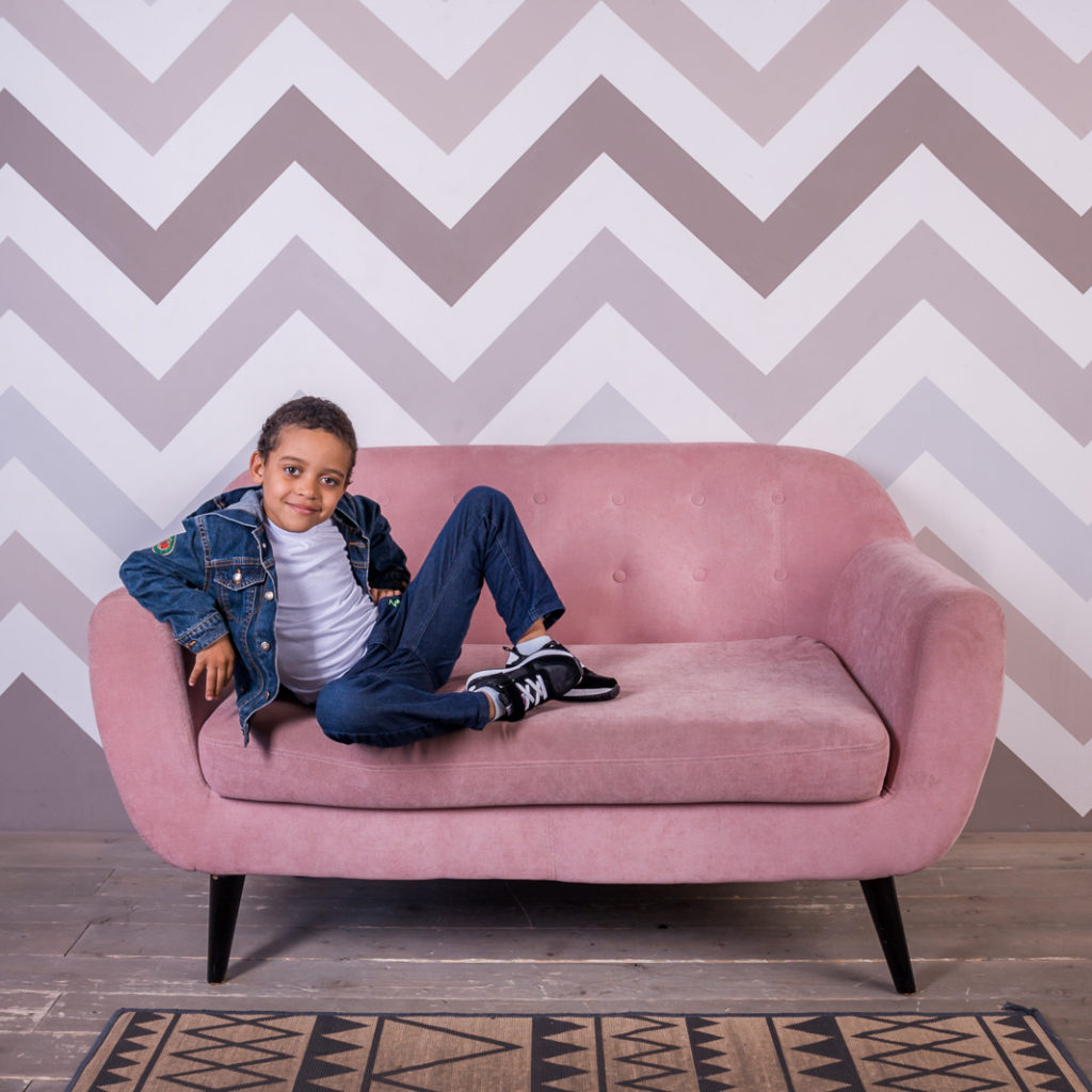 темнокожий мальчик сидит на розовом диване и думает, какую фотостудию выбрать